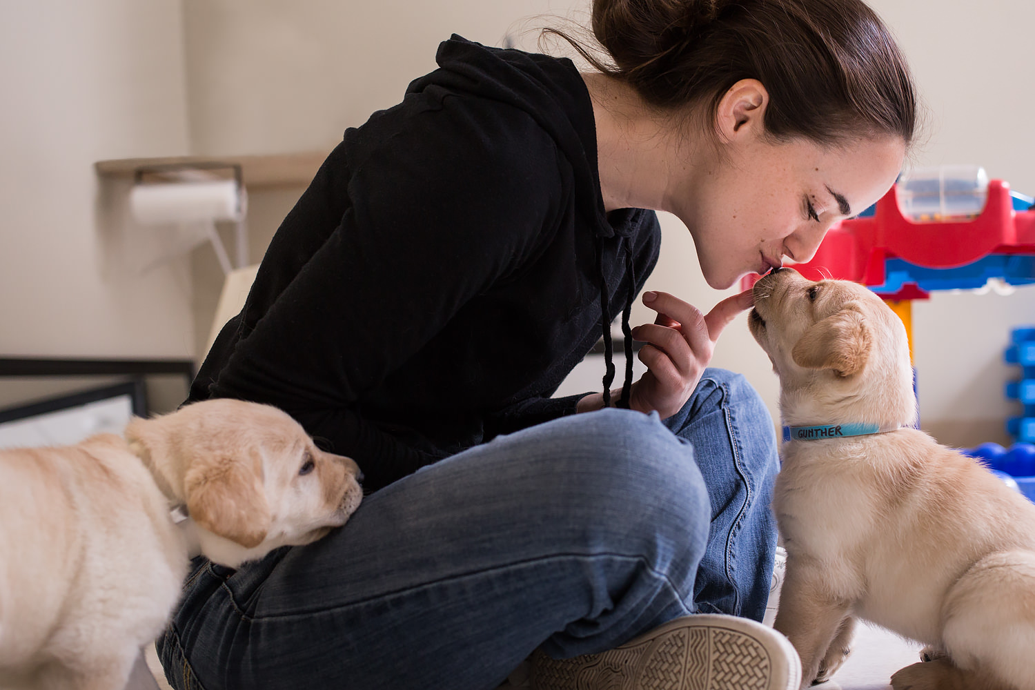 Guiding Eyes volunteer Lauren kisses pup Grant on the nose.
